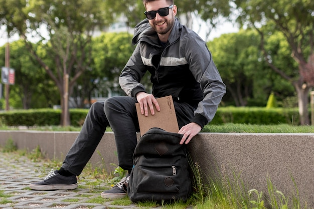 Smiling man putting book in backpack