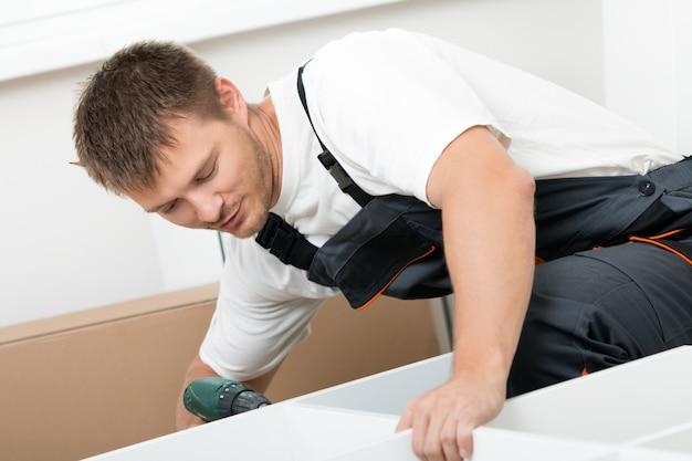 Улыбающийся человек, собирающий мебель для самостоятельной сборки в новом доме. сделай сам, новый дом и концепция переезда