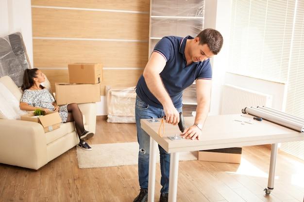 新しい家で組み立て家具を組み立てる笑顔の男。新しい家の家具。