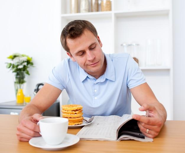 朝食を取っている間に新聞を読んでいる笑顔の男