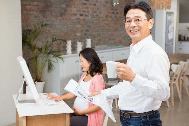 Smiling man reading newspaper and having coffee at home while pregnant wife is using laptop