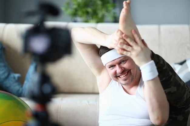 カメラの脚のストレッチで記録する笑みを浮かべて男
