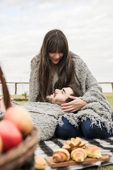 Smiling man relaxing on her girlfriend's lap at picnic