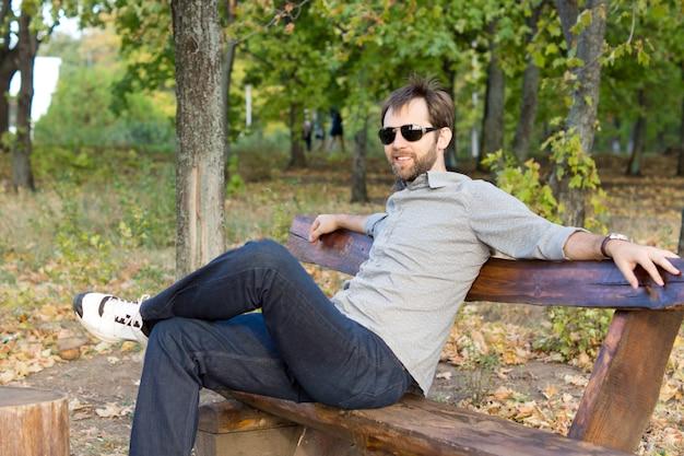 Улыбающийся человек расслабляется на скамейке в парке, сидя, раскинув руки вдоль спины, наслаждаясь солнцем