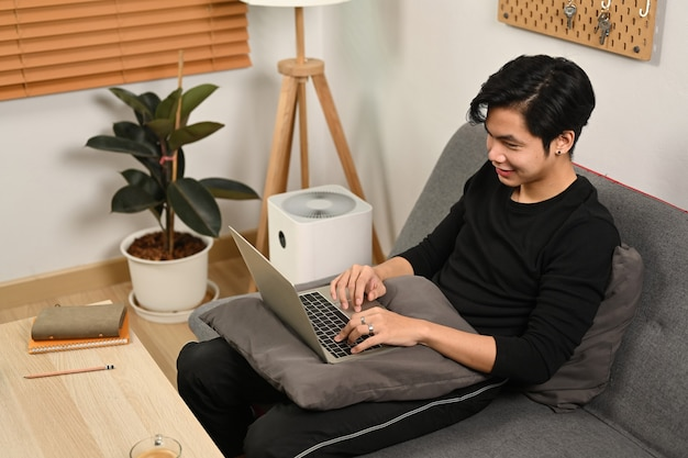Улыбающийся человек расслабляющий на диване и с помощью портативного компьютера.