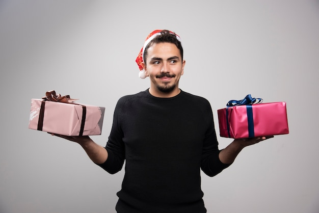 A smiling man in a santa's hat holding a new year's gifts .
