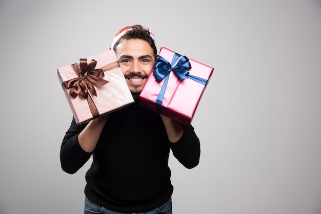 Un uomo sorridente con il cappello di babbo natale in possesso di regali di capodanno.