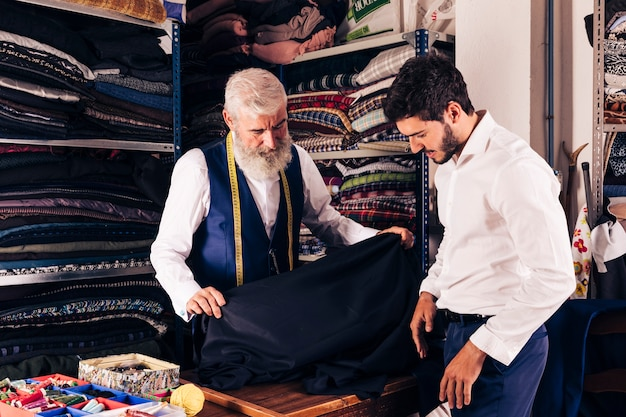 Smiling man seller displaying blue fabrics to young customer in textile shop