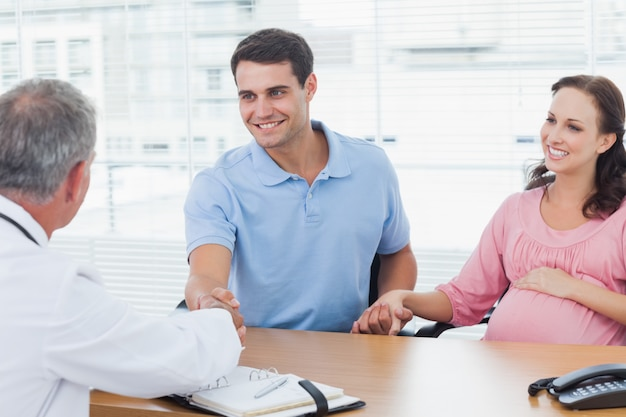 Smiling man shaking hands with his doctor while holding his expecting wifes hand