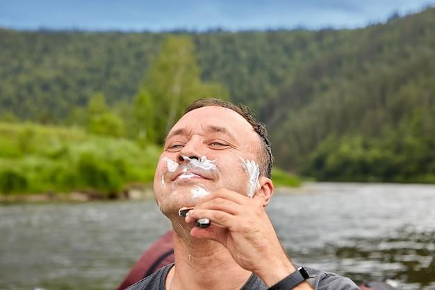 笑顔の男性は、シェービングフォームとかみそりを使用して自然の中で剃ります。
