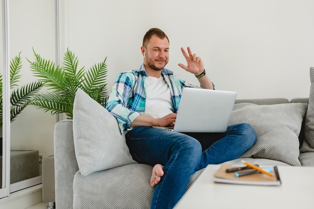 Smiling man in shirt sitting relaxed on sofa at home at table working online on laptop from home