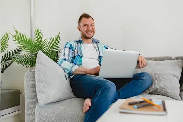 Uomo sorridente in camicia seduto rilassato sul divano a casa al tavolo lavorando online su laptop da casa