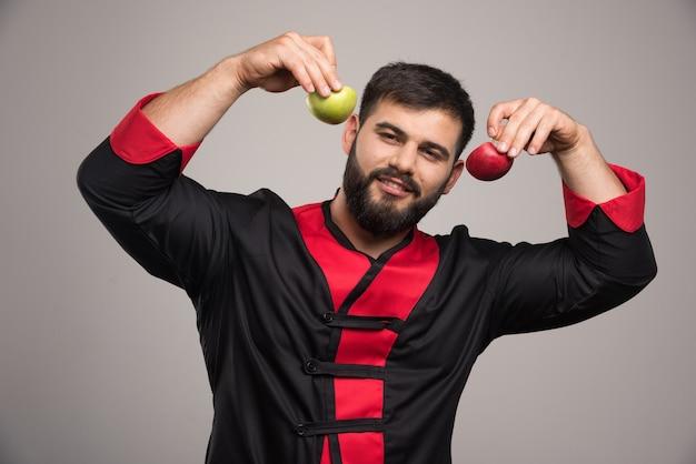 新鮮なリンゴのスライスを示す笑顔の男。