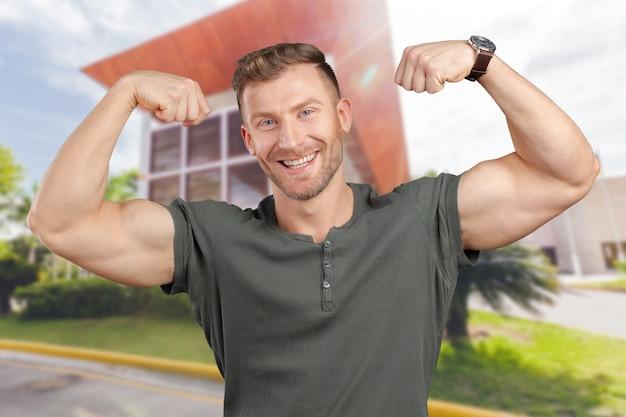 Smiling man showing biceps