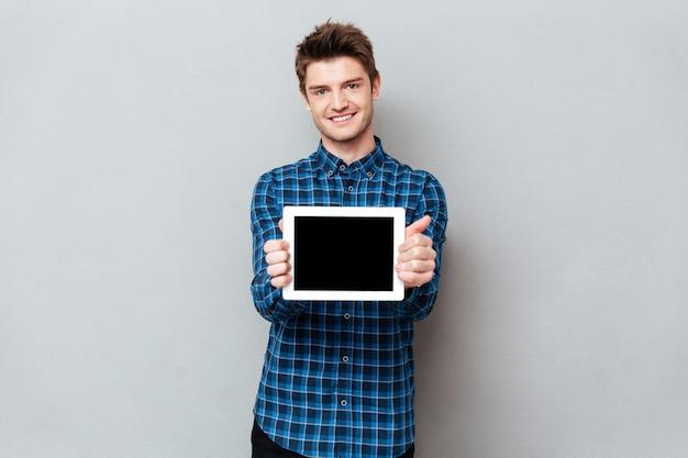 Улыбающийся человек, показывая пустой экран планшетного компьютера