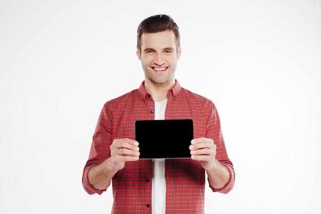 空白のタブレットコンピューターの画面を示す笑みを浮かべて男