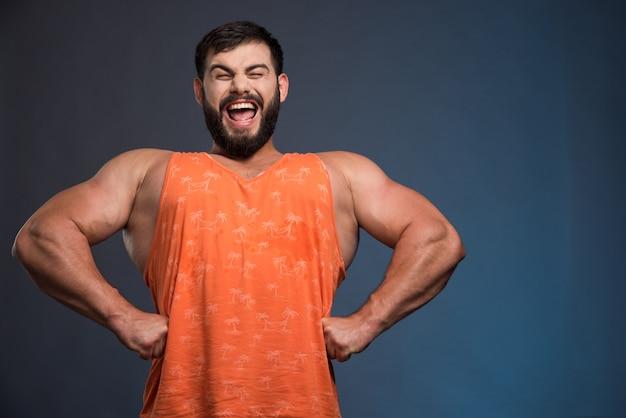 Улыбающийся человек показывает свои мышцы на синей стене.
