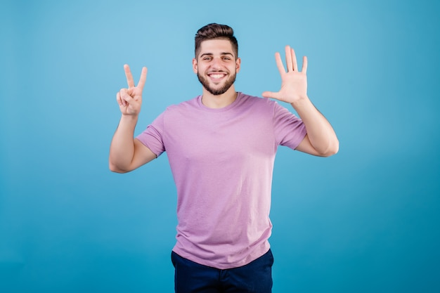 Smiling man showing seven fingers isolated on blue