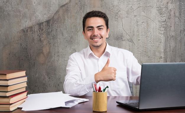 엄지 손가락을 보여주는 책상에 앉아 웃는 남자. 고품질 사진