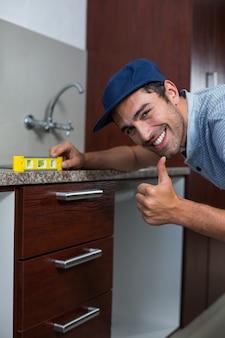 Smiling man showing thumbs up while using spirit level