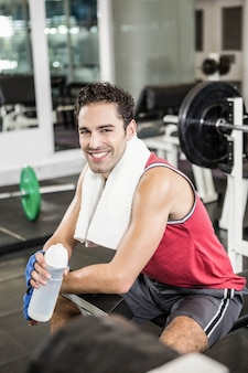 Smiling man sitting on bench and holding bottle of water in the gym