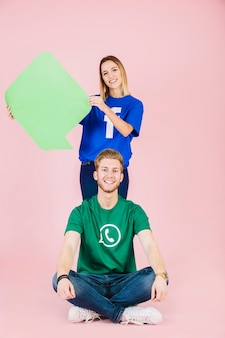 Smiling man sitting in front of woman holding empty green speech bubble