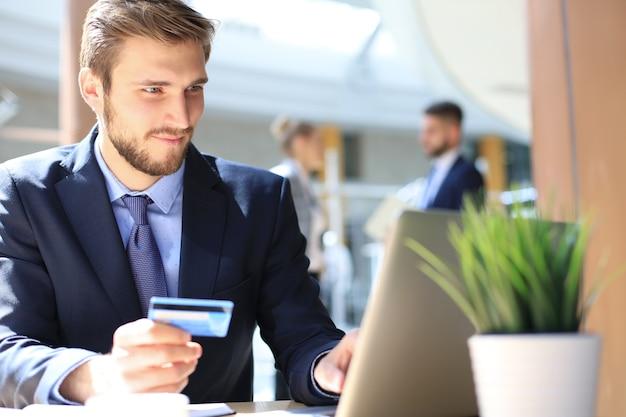オフィスに座って、彼のラップトップでクレジットカードで支払う笑顔の男。