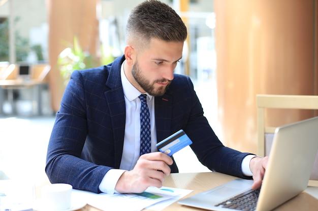 Улыбающийся человек сидит в офисе и платит кредитной картой со своим ноутбуком.