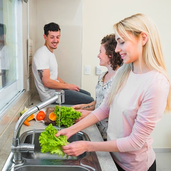 Smiling man sitting on kitchen worktop looking at two women cleaning the lettuce