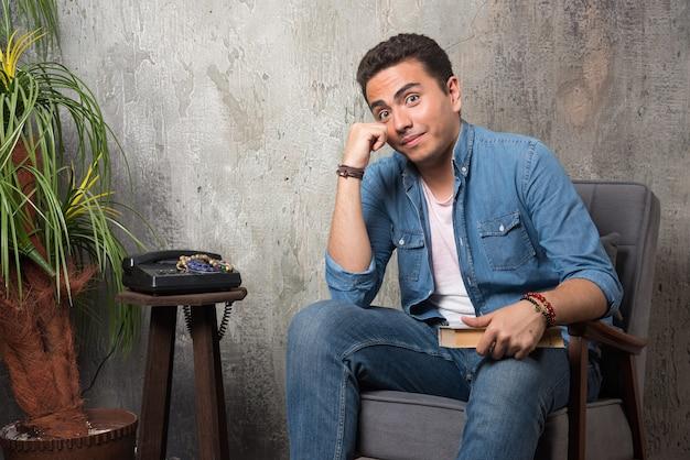 大理石の背景の本と椅子に座っている笑顔の男。高品質の写真
