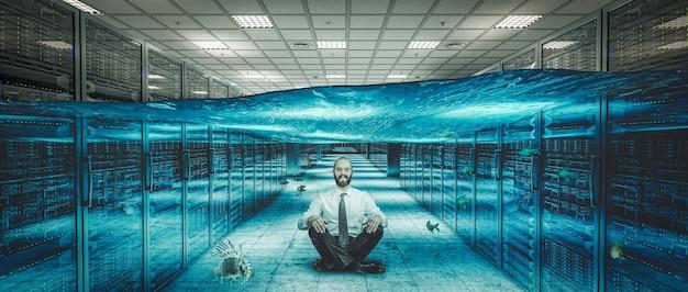 Улыбающийся человек сидит на полу затопленного серверного центра.