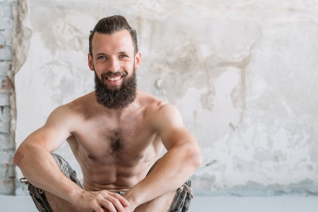 Smiling man sitting resting after workout. sport exercising and fitness lifestyle concept.