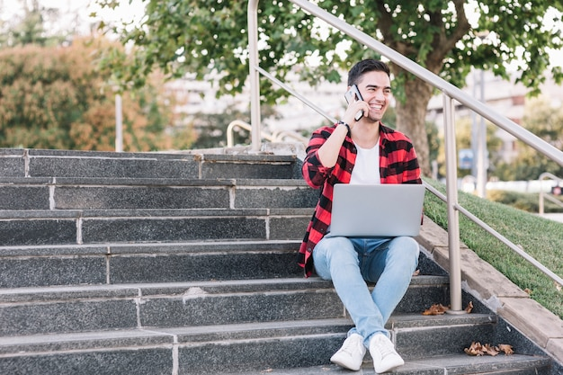 Smiling man sitting on stairway talking on smartphone