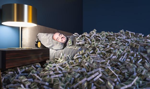 Улыбающийся человек спит в кровати, покрытой деньгами в долларах. понятие богатства.