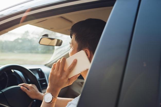 笑顔の男は白い車の中でスマートフォンで話します。ビジネスマンは車の運転と携帯電話での会話に成功しました。