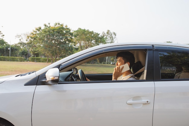 웃는 남자는 흰색 차에 스마트 폰에 말합니다. 사업가 성공적으로 그의 차를 운전하고 휴대폰에 말하기.