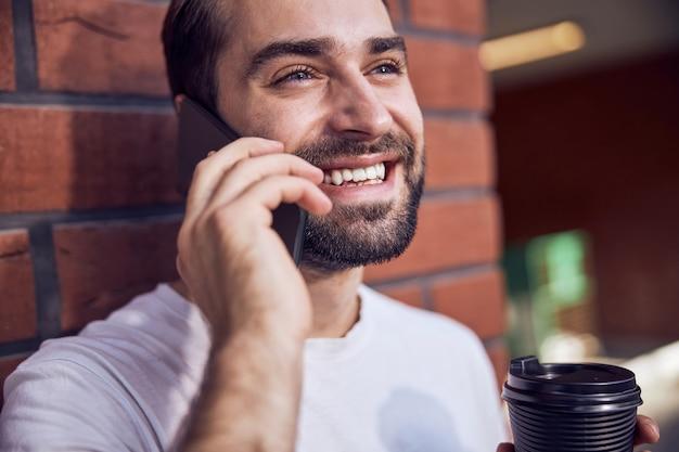 커피 ouydoor와 스마트 폰으로 말하는 웃는 남자를 닫습니다.