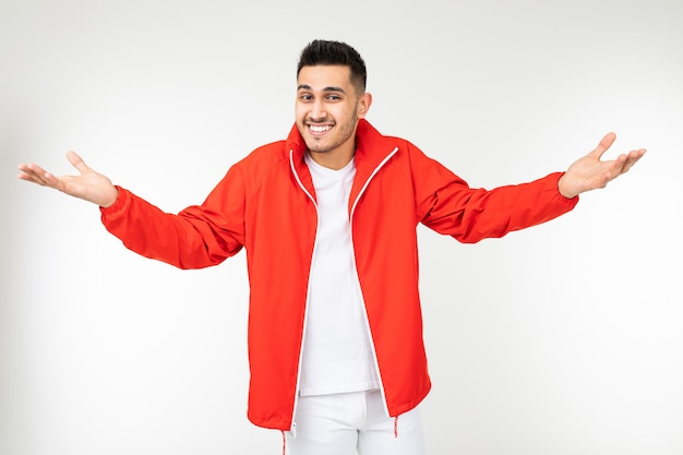 Smiling man in a sports red suit with open arms on a white background with copy space