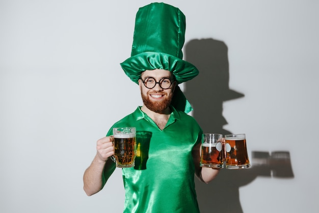 Smiling man in st.patriks costume holding cups