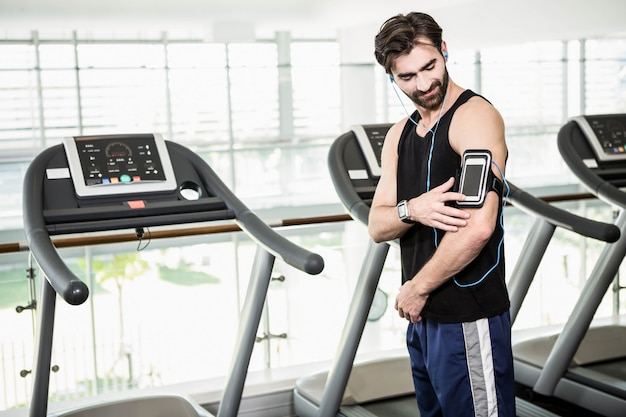 Smiling man standing against treadmills at the gym