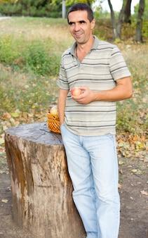 新鮮なジューシーなリンゴを手に、田舎でのこぎりで切った木の幹の横に立っている笑顔の男