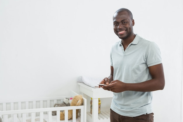 Smiling man standing next to a cradle and text messaging on mobile phone at home
