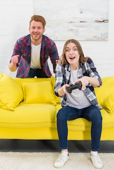 Smiling man standing behind the excited woman playing the video game in the living room
