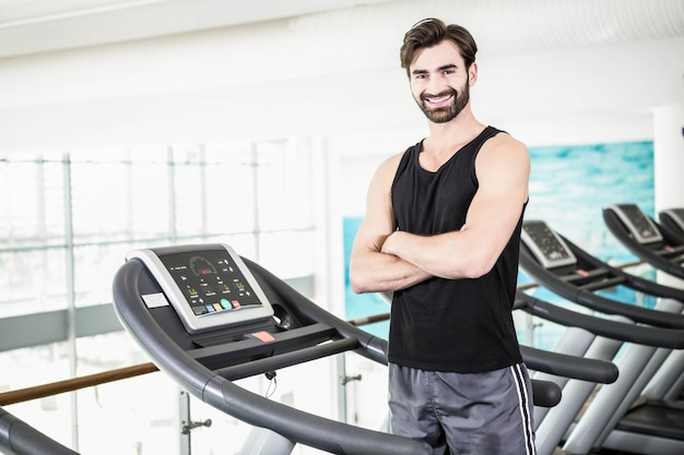 Smiling man standing on treadmill with arms crossed at the gym