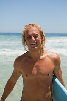 Smiling man standing in the water while holding his surfboard