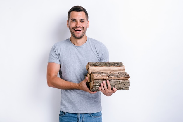 Smiling man standing over white studio background and holding a lot of firewood at his hands. studio image, isolated on white background