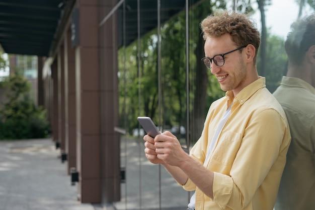 거리에서 온라인 쇼핑을 하며 웃고 있는 남자 세련된 안경