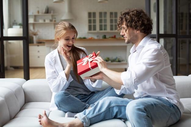 Улыбающийся мужчина удивляет свою девушку подарком дома. дарить подарки.