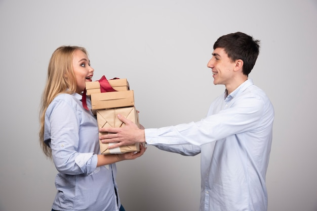 Smiling man surprises his girlfriend with presents over gray wall.