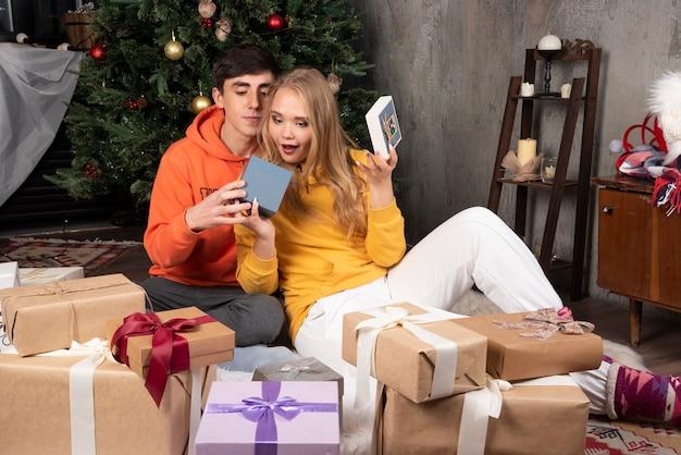 웃는 남자는 크리스마스 트리 근처에 선물로 여자 친구를 놀라게 합니다.
